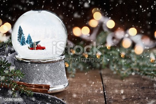 Rustic image of a snow globe with old pick up tuck hauling a Christmas tree surrounded by pine branches, cinnamon sticks and a warm gray scarf with gently falling snow flakes.