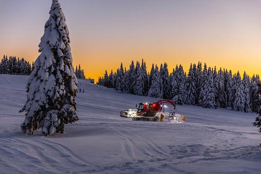Snow groomer on ski slope