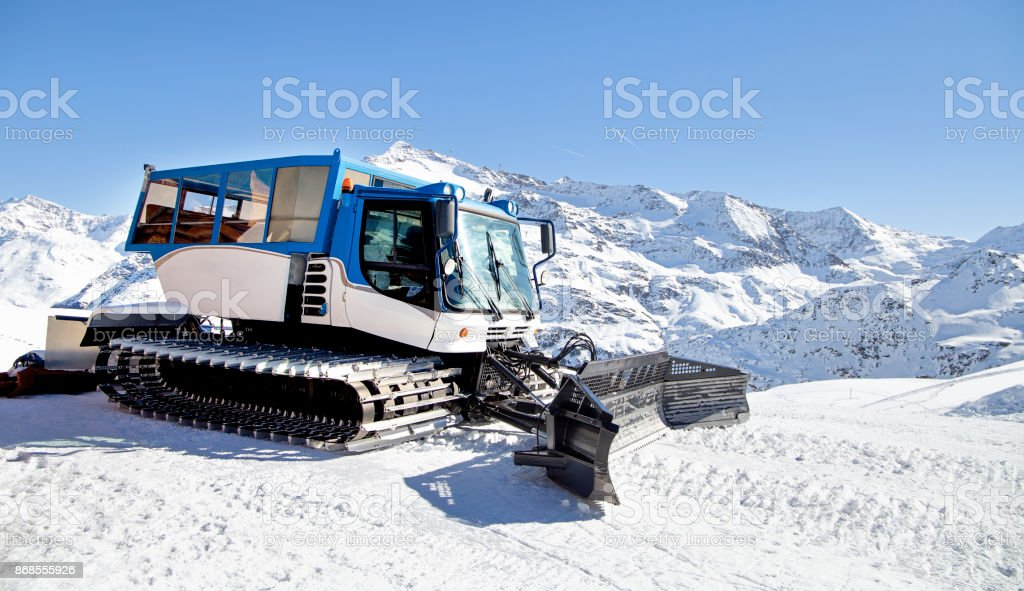 Snow grooming machine on snow hill ready for skiing slope preparations in Alps, Europe ski resort stock photo