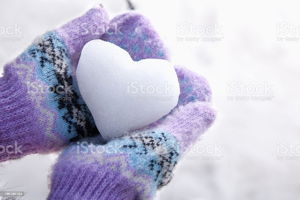 Snow Heart in Hands with Mittens stock photo
