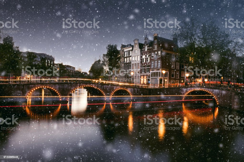 Snow in Amsterdam canals at night in winter stock photo