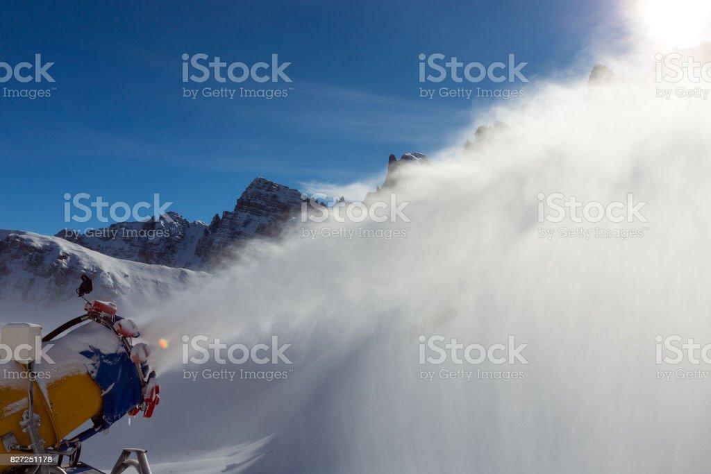 Snow making Cannon dispersing fresh snow on ski piste stock photo