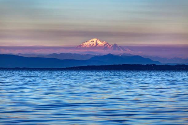montagne de neige à un coucher de soleil brumeux avec de l'eau de mer au premier plan - mont baker photos et images de collection