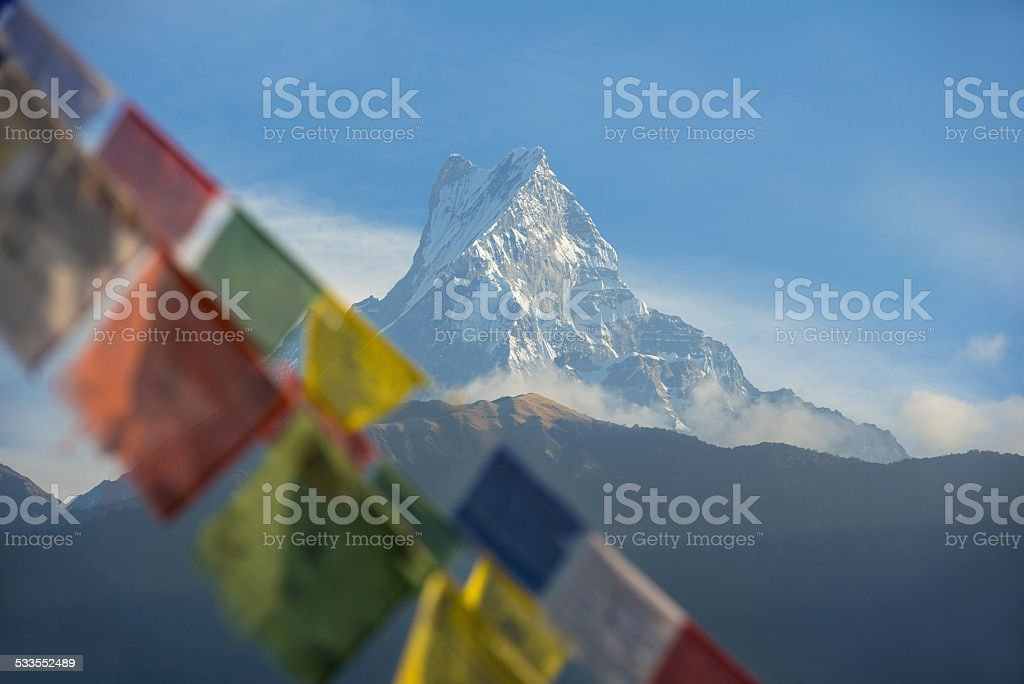 Snow mountain in Nepal with blurred prayer flags in foreground stock photo