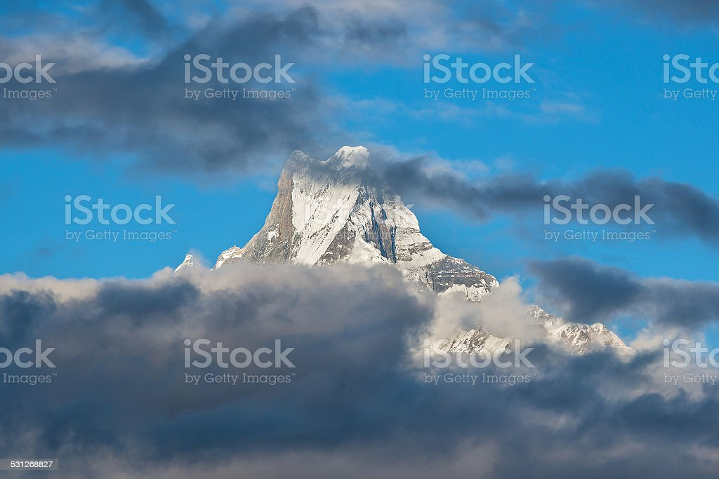 Snow mountain partly obscured by clouds stock photo