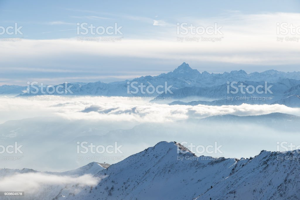 Snow mountains in backlight, bright sunny day winter on the Alps, high snowcapped mountain peaks, fog and clouds in the valleys below. stock photo