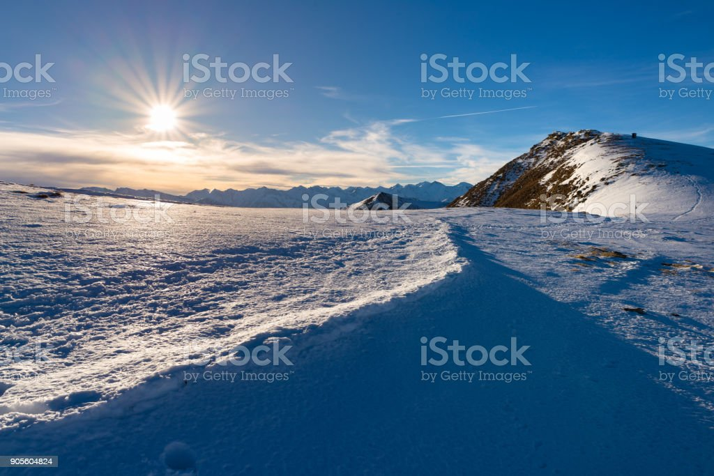 Snow mountains in backlight, bright sunny day winter on the Alps, sun glowing over high snowcapped mountain peaks. stock photo