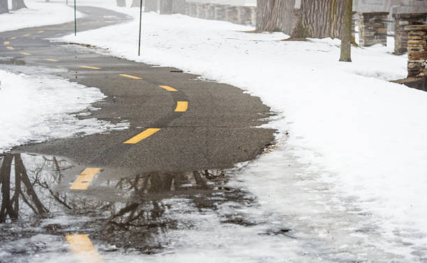 Snow on a winding bike path on a foggy winter day stock photo