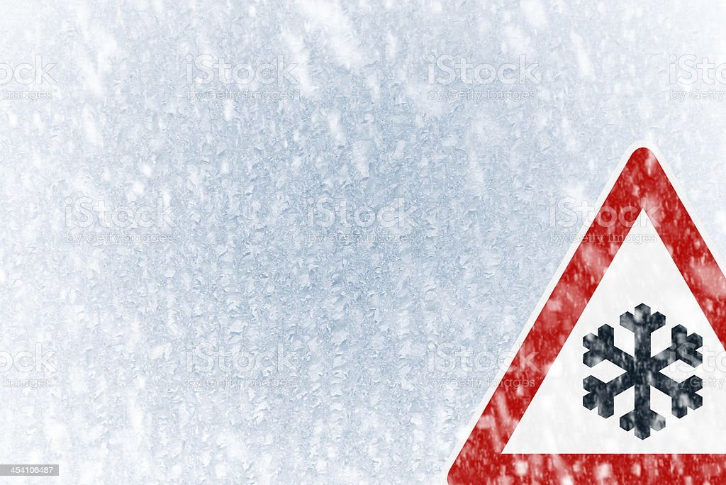 Snow on an ice covered windshield with warning sign stock photo