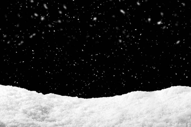 Snow on black background with snowfall. Snowdrift backdrop in winter season. stock photo