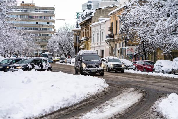 Schnee auf Autos am Morgen. Wintersaison und eisige Autos auf der Straße im morgendlichen Rush hour Verkehr von Bukarest, Rumänien, 2020 – Foto