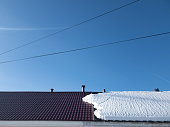 The now on half the roof of the house. In half. Melting snow on the roof.