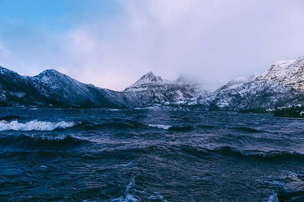 snow on mountain peaks over lake - cradle mountain stock photos and pictures