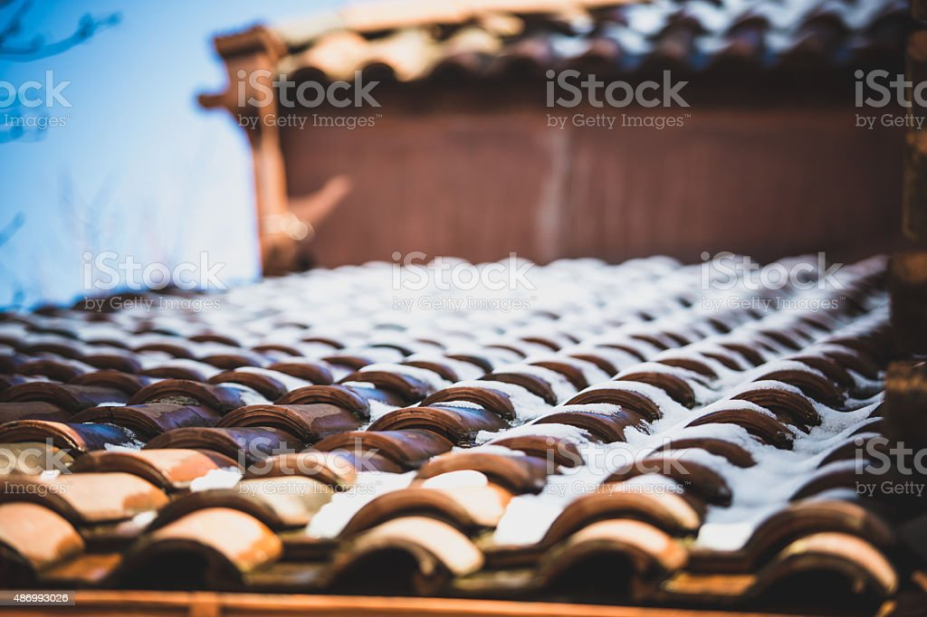 snow on red tiled roof stock photo