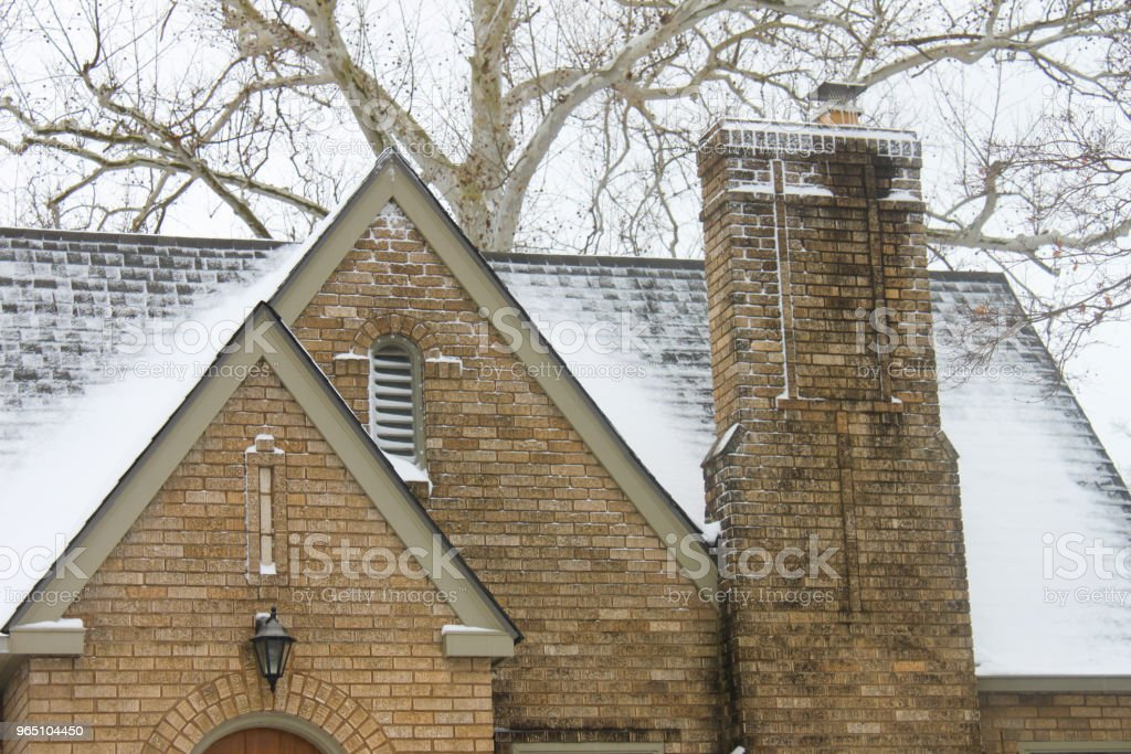Snow on roof with chimney of yellow brick historic home with birch tree in the background royalty-free stock photo