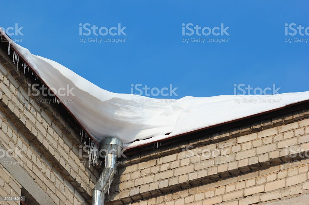 Snow on roof with winter gutterand icicles stock photo