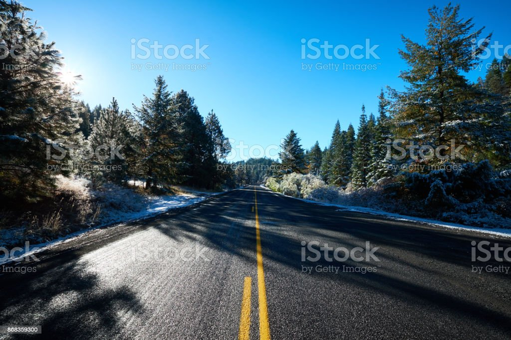 Snow on side of the road in the forest stock photo