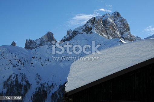 istock Snow on the roof of a mountain refuge at the valles pass and the Pale di San Martino mountain group seen from the road to Passo Valles during the winter season. Dolomites in South Tyrol, Italy. 1200119058