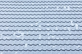Close-up tiled roof texture covered with a thin layer of snow on a frosty day. Winter pattern