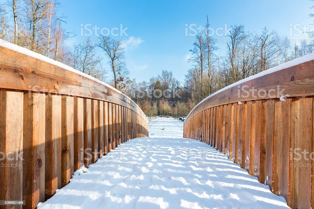 Snow on wooden bridge in forest area stock photo