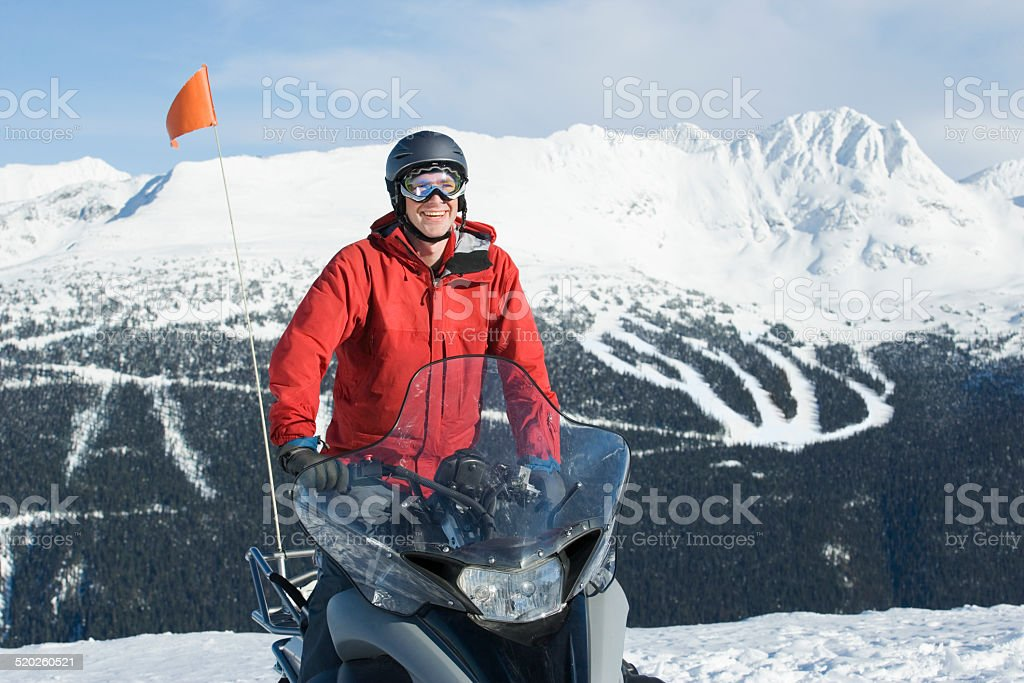 Snow patrol rescue worker sitting on snowmobile stock photo