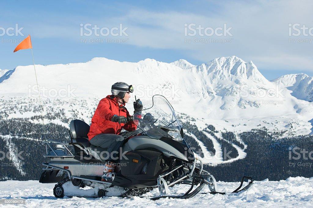 Snow patrol rescue worker sitting on snowmobile, using walkie talkie stock photo