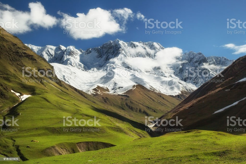 Snow peaks of Caucasian mountains, springtime outdoor background stock photo