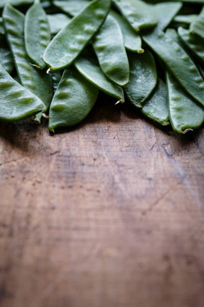 Snow Peas on a Rustic Wooden Surface stock photo