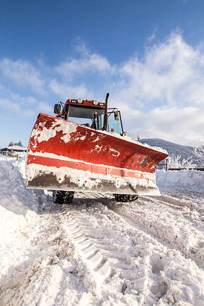 Snow plough cleaning snowy road stock photo