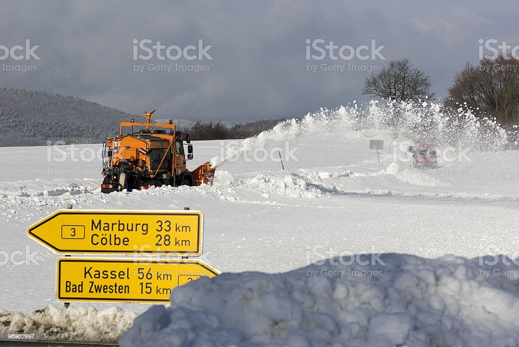Snow plough is clearing the blocked country road royalty-free stock photo