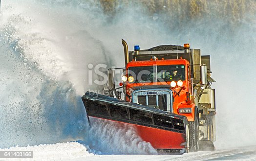Orange snowplow makes its way down the highway, clearing the snow as it goes.  Picture was taken in Interior Alaska on a bright day in winter.