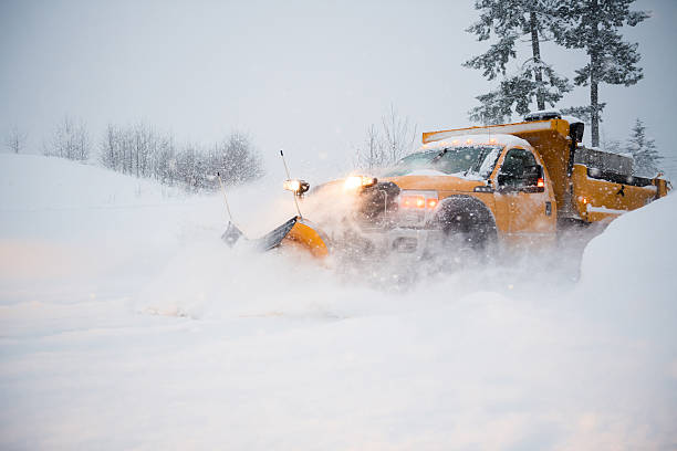 snow plow clearing a snowy highway - blizzard stock photos and pictures