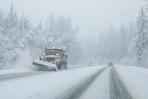 Snow plow clearing highway during snow storm. stock photo