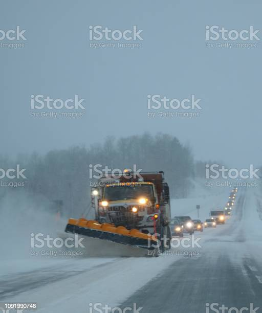 Photo of Snow plow moving drifting snow of road in squalls with trail of cars following