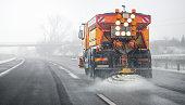 istock Snow plow salting street in winter time. Orange truck deicing. 1222260595