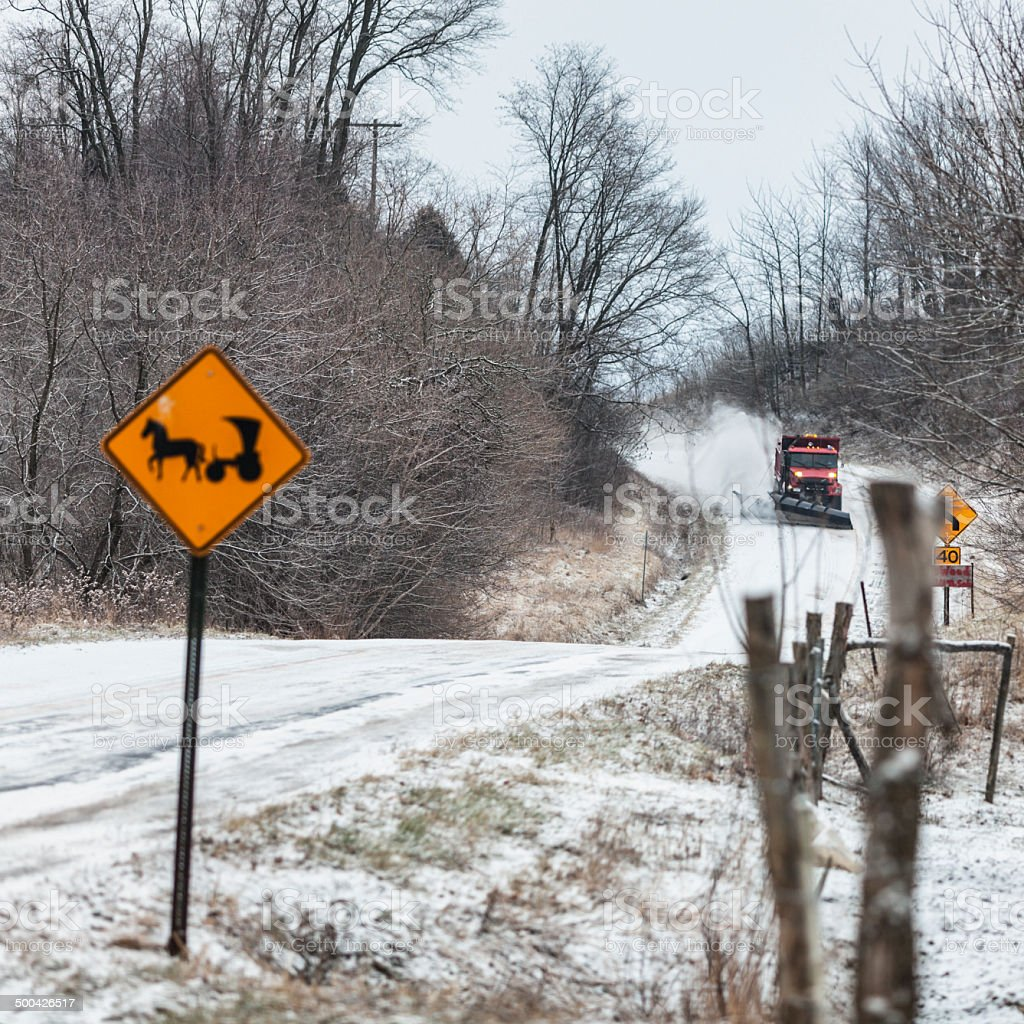 Snow Plow Truck Approaching Amish Horse And Buggy Road Sign stock photo