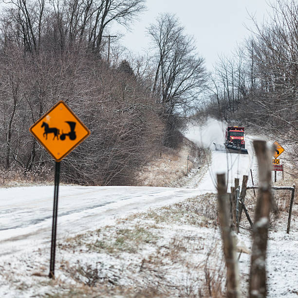 Snow Plow Truck Approaching Amish Horse And Buggy Road Sign A large modern dump truck snow plow throwing and blowing snow on a dangerous curve is approaching an Amish horse and buggy caution road sign at the edge of this rural winter snow covered road. Finger Lakes region of western New York State. anachronistic stock pictures, royalty-free photos & images