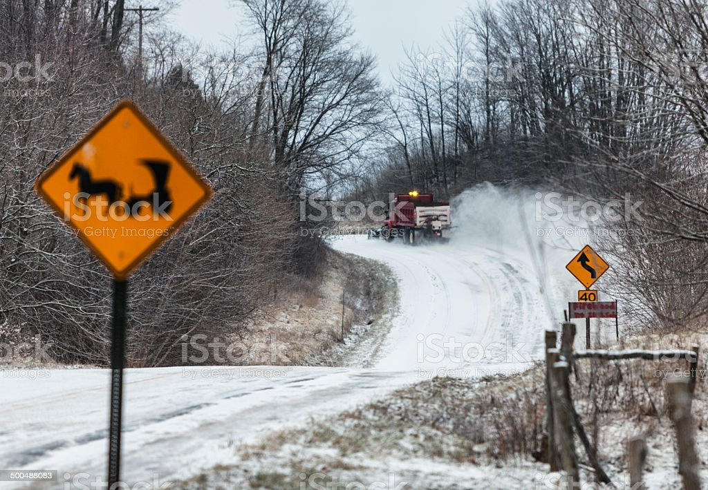 Snow Plow Truck Beyond Amish Horse And Buggy Road Sign stock photo