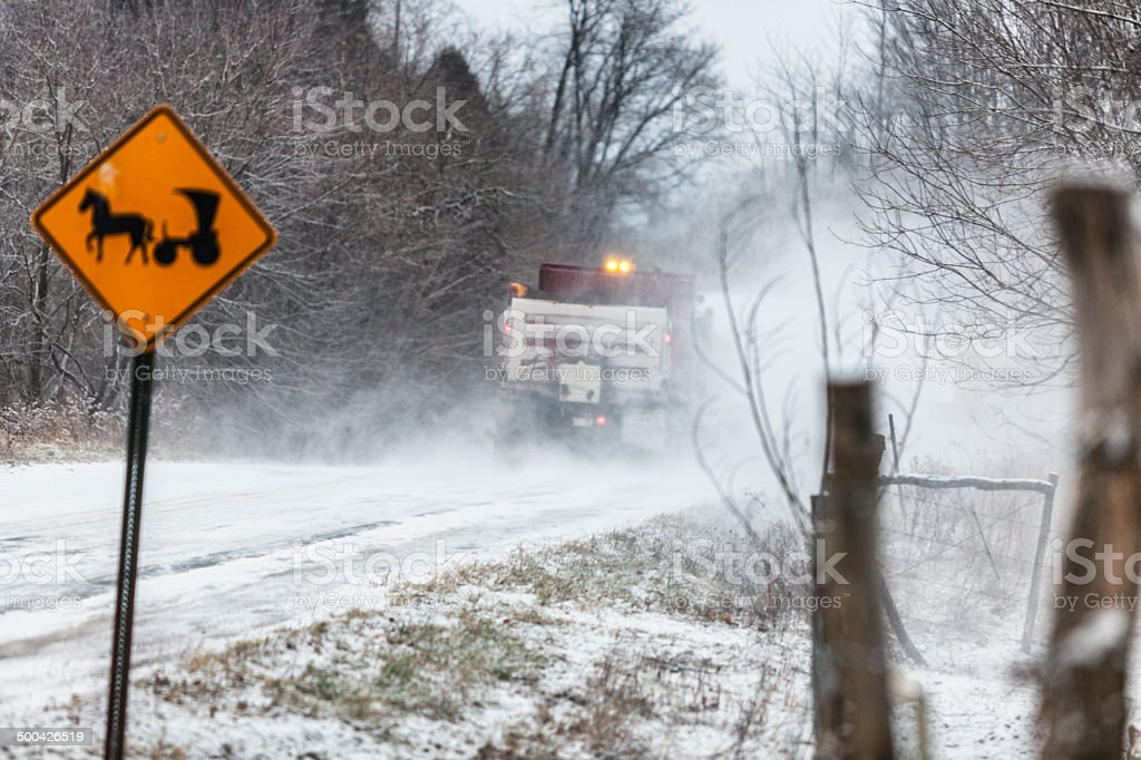Snow Plow Truck Passing Amish Horse And Buggy Road Sign stock photo