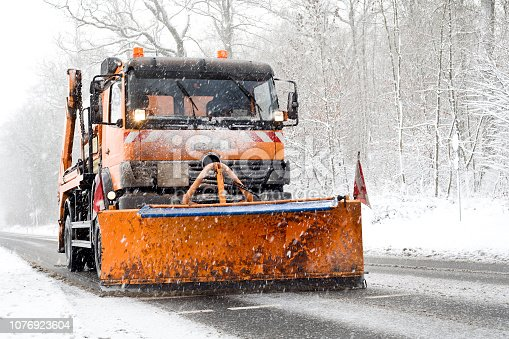 Snow plow truck in action - winter road conditions, heavy snowfall, minor motion blurring