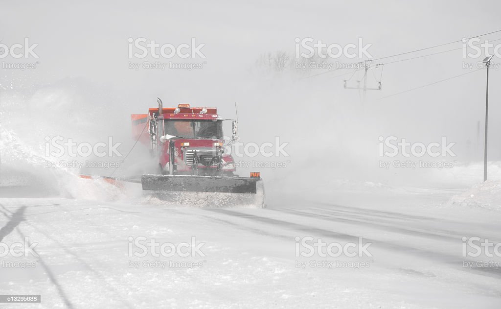 Snow plower truck in blizzard. stock photo