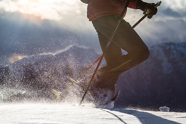 neige soulevé par un homme marche en raquettes. - raquette photos et images de collection