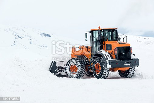 Rear quarter view of a large front end loader being utilized for snow removal