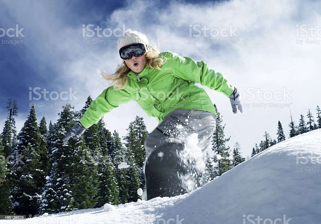 snow ride view of a young girl snowboarding in winter environment Activity Stock Photo