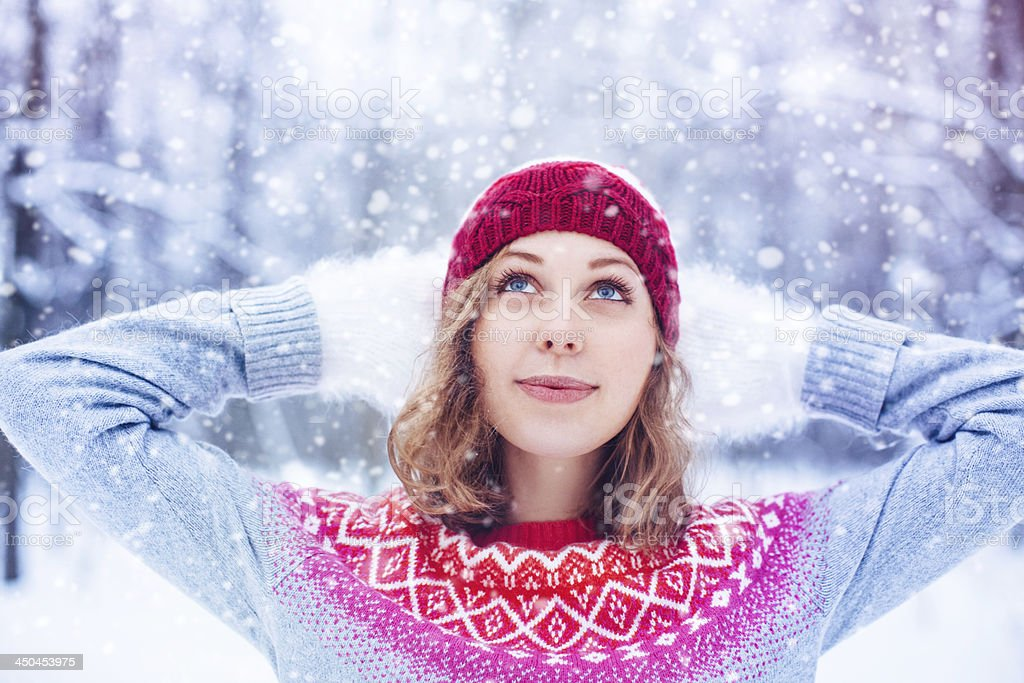 A snow scene of a young lady wearing a fleece and snowcap  stock photo