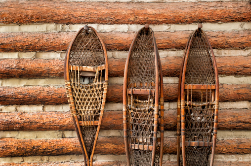 3 pairs of vintage snow shoes hanging on a cabin