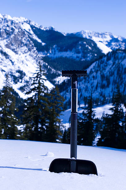 snow shovel in the mountains stock photo