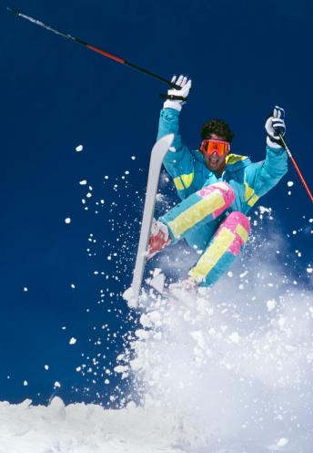 Snow Skier with Fresh Snow Jumping Towards Camera.