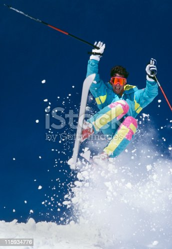 Snow Skier with Fresh Snow Jumping Towards Camera.