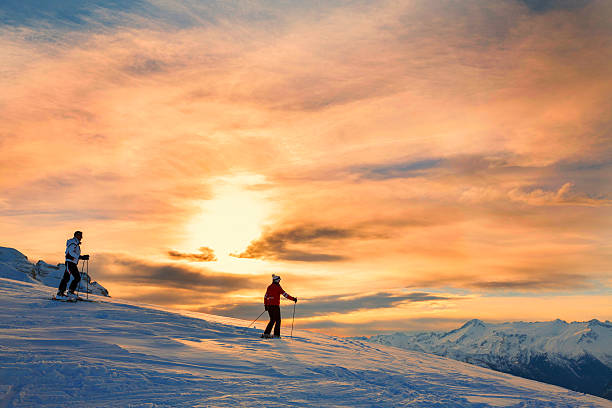 Snow skiers couple  Enjoying a beautiful winter mountains  sunset landscape Snow skiers couple, off piste skiing. Mature women and men enjoying a beautiful winter mountains  sunset landscape. The  orange sky in the background. dolomites stock pictures, royalty-free photos & images